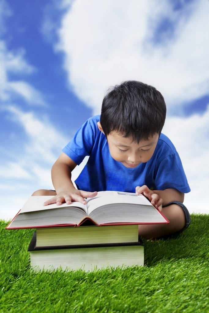 MakoStars LLC/ bigstock Boy Practice Reading Outdoor 33270632
